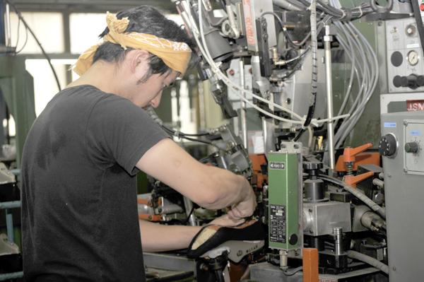 写真:インソールの踵部分に数秒で順に8本の釘(釘の本数は形状によって異なる)を打てる機械で作業中の職人さん