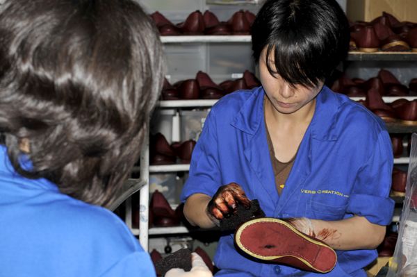 写真:職人の皆さんは全員「Verb Creation」の刺繍の入った制服とおそろいの靴を着用で作業。こちらの職人さんは靴に染色中