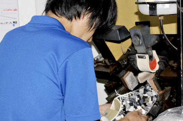写真:OEMの靴のアッパーを木型にはめている職人さん