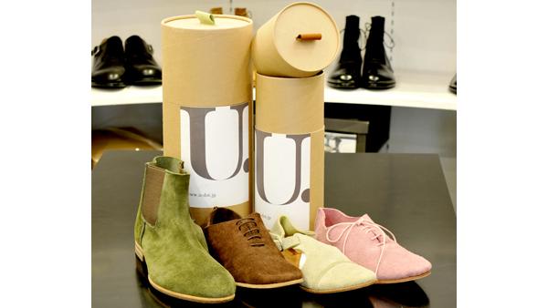 写真:自社ブランド「U.(ユードット)」は遊びがコンセプト。 筒状の箱に靴(ブーツも!)が入るようになっている。箱の取っ手の色は靴の色と一致する。国内外で販売。