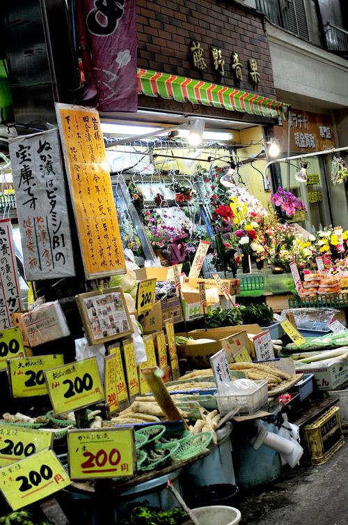 「ジョイフル三ノ輪商店街」のアーケードにに入って、ほんの20メートル程歩いたら、お漬物の匂いが「藤野青果」がそこにあることを教えてくれます。右の造花は奥さんの手作り。