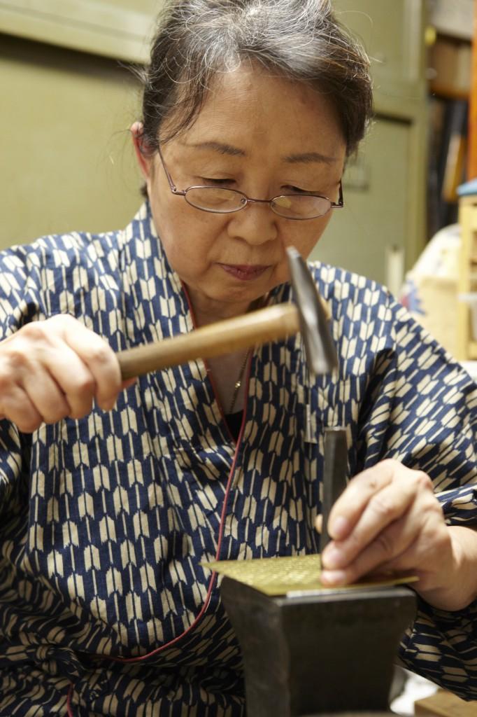 写真:たがねで模様を打ち付ける塩澤さん