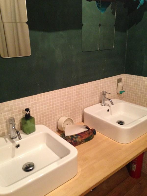 2階にある洗面スペース。壁は黒板塗料で深緑。洗面もタイルも鏡も四角に。