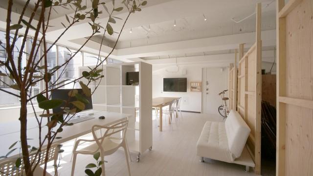 手前の白い机がフリーアドレス。奥の木製の机がミーティングスペースです