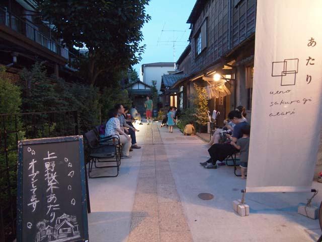 上野桜木あたりのエントランス。木造家屋の間の路地に、思い思いに人が集まってきます