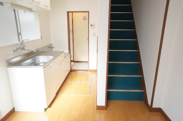 1階の玄関から見た様子。青いカーペットの貼った階段も味があります。奥に風呂場・トイレあり。